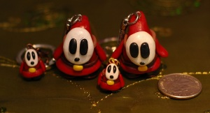 These are Shy Guys from Super Mario Brothers. The original shy guy is pretty cute, but these are just plain creepy in my opinion. Their creepiness makes them cool, though.