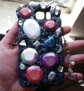 Cam O Chan's friend ordered a custom case based on the TV show StevenUniverse. He wanted it to be outer space themed and incorporate his favorite characters. The large clay gemstones represent a few of the characters. The black frosting is coated with blue and purple shimmer powder, but that didn't come out very well in the picture. Lastly, there is a dangly charm of the lovable character Cookie Cat.